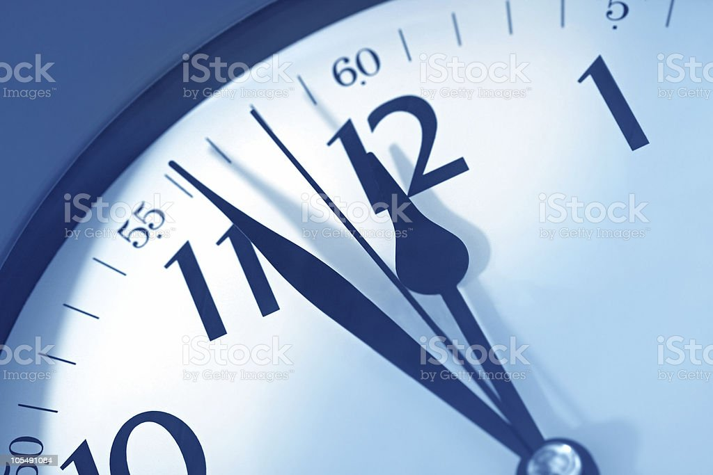 Close-up of analog clock counting down to midnight deadline stock photo