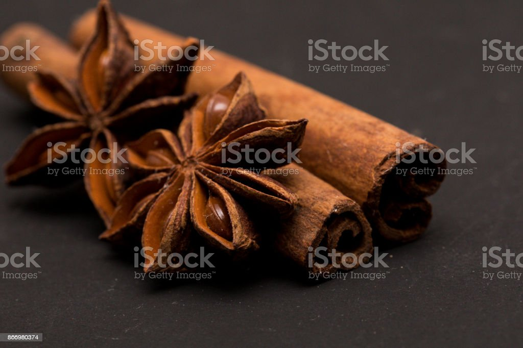 Closeup of anise star and cinnamon stick on dark background stock photo