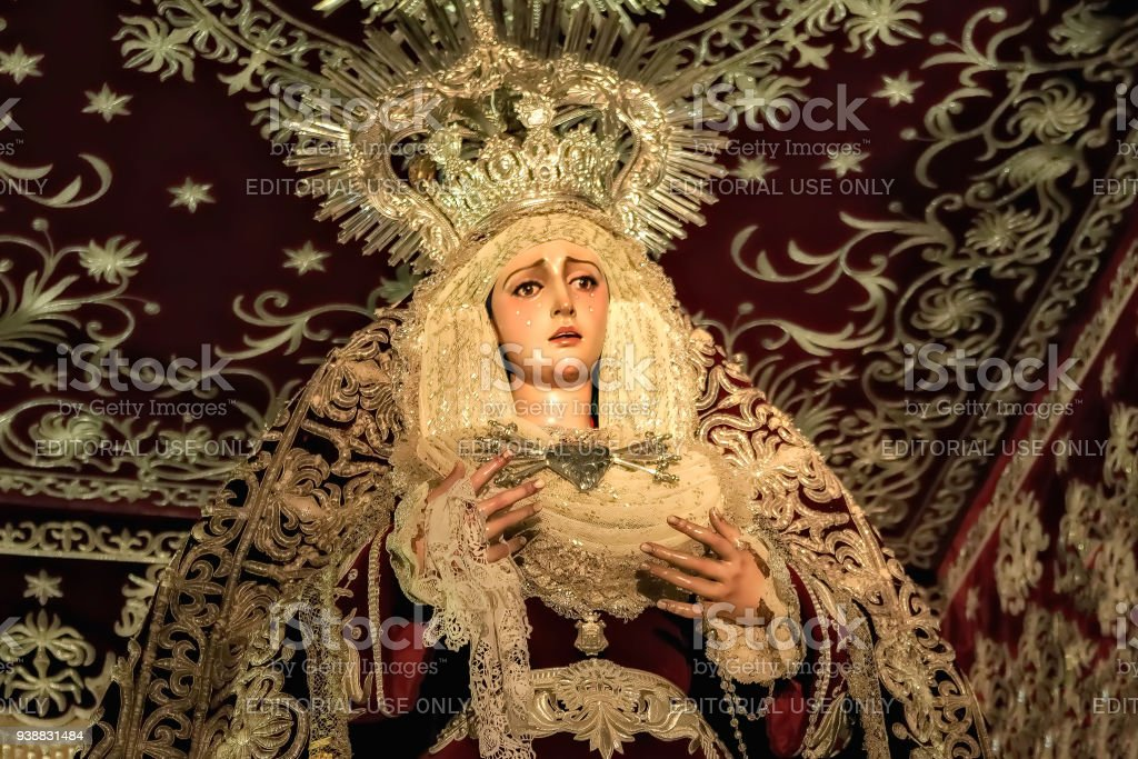 Closeup of antique wooden sculpture depicting Virgin Mary in a religious float during Holy Week procession in Huelva. stock photo