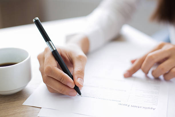 Closeup of Applicant Completing Application Form Cropped view of woman holding pen and filling out application form at table with focus on hand with pen application form stock pictures, royalty-free photos & images