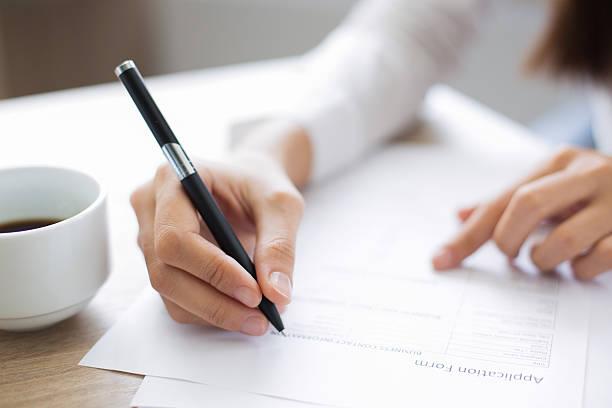 closeup of applicant completing application form - bewerbung lebenslauf stock-fotos und bilder