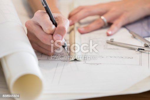 476601452 istock photo Closeup of architect's hands as she uses ruler in blueprint drawing 838945324