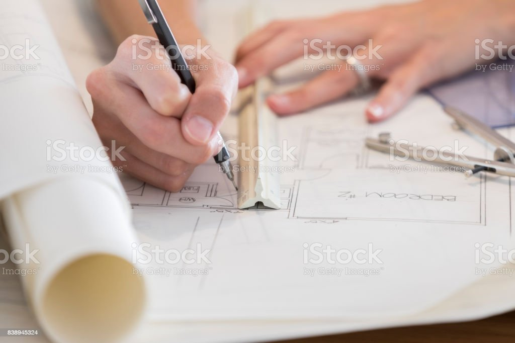 Closeup of architect's hands as she uses ruler in blueprint drawing stock photo