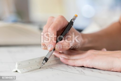 istock Closeup of architect's hands drawing blueprint using ruler 823845672