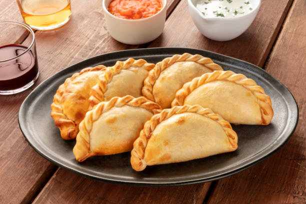 A closeup of Argentinian empanadas with sauces and wine on a dark rustic wooden background stock photo
