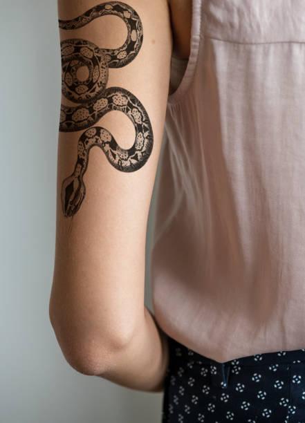 nahaufnahme von einer frau am arm tattoo - tattoos frauen arm stock-fotos und bilder
