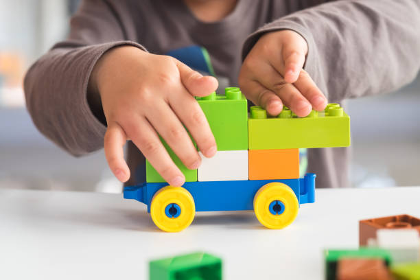 Closeup of asian kid's hand playing plastic  blocks, puzzle. Concept of education and development. stock photo
