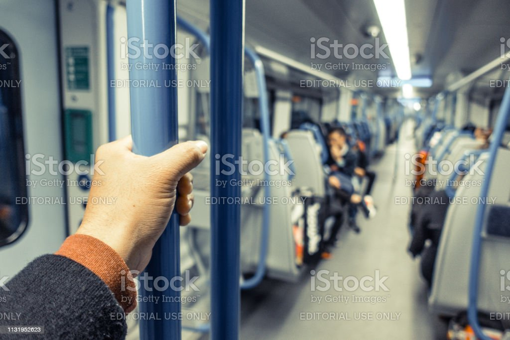 Closeup of Asian man hand holding handrail or pole inside the train...
