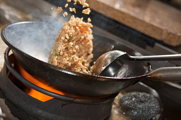 Close-up of Asian stir-fry cooking in a wok Closeup of fried rice being cooked in wok fried rice stock pictures, royalty-free photos & images
