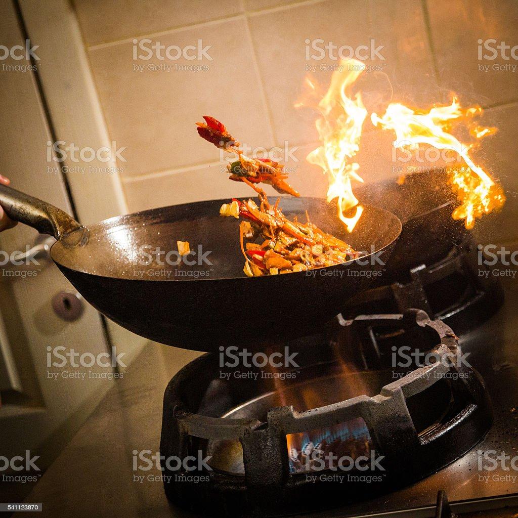 Close-up of Asian wok stir-frying on gas stove. stock photo