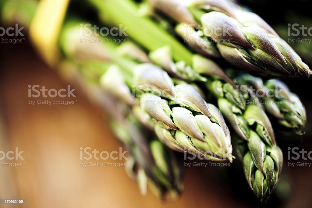 Close-up of asparagus shoots on wooden table stock photo