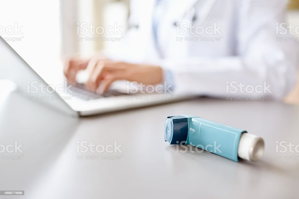 Close-up of asthma inhaler with doctor using laptop at desk stock photo