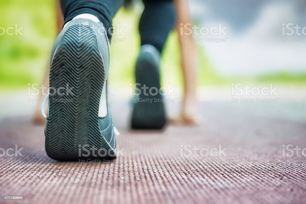 Close-up of athletes shoe at starting line of track stock photo