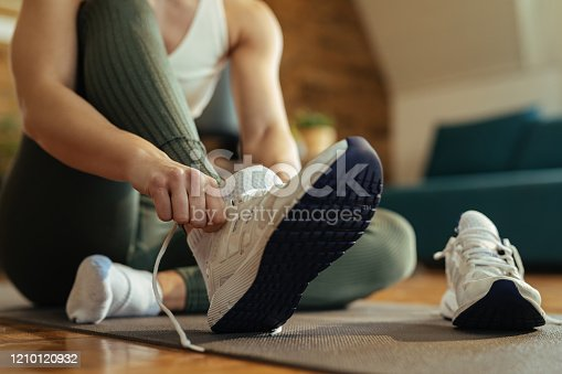 Close-up of sportswoman putting on sneakers.