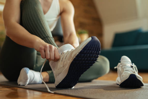 Close-up of athletic woman putting on sneakers. stock photo