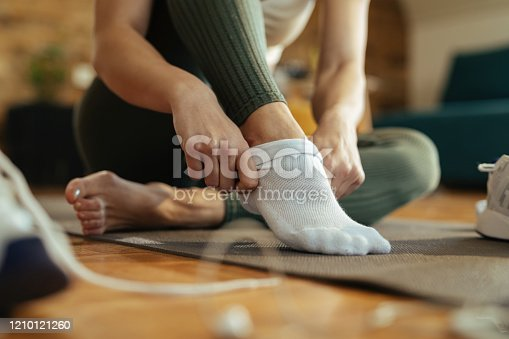 Close-up of sportswoman wearing white socks while preparing for workout at home.