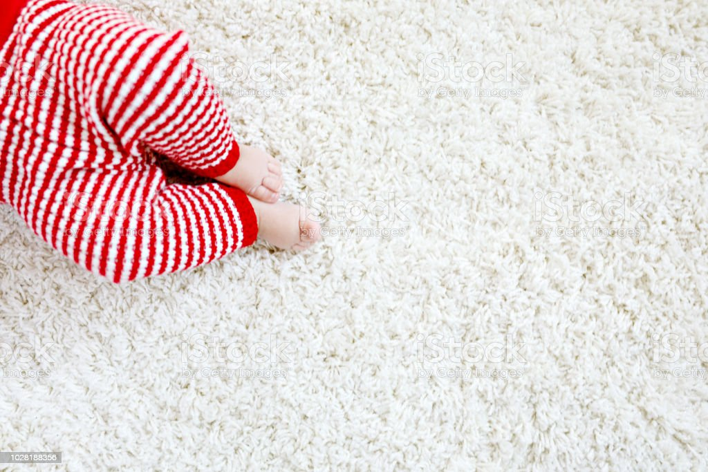 Close-up of baby body and legs in red Santa Clause trousers on Christmas stock photo