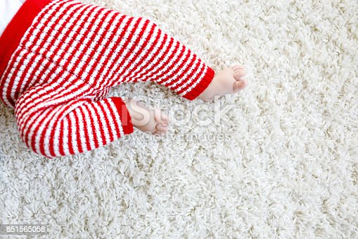 istock Close-up of baby body and legs in red Santa Clause trousers on Christmas 851565058