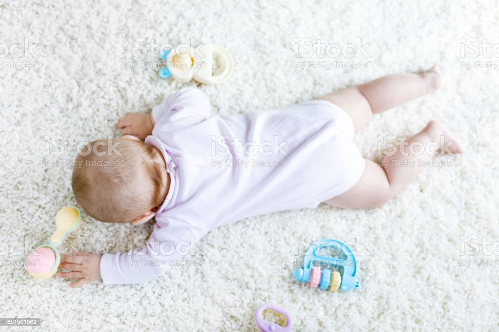 Close-up of baby body and legs with lots of colorful rattle toys. stock photo
