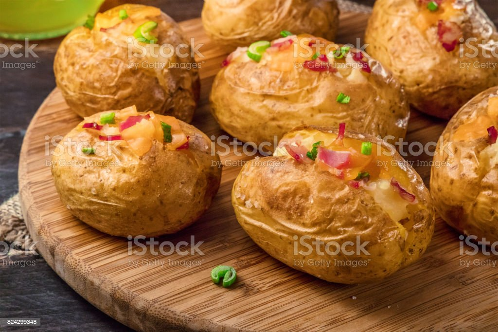 Closeup of baked potatoes with cheese and bacon stock photo