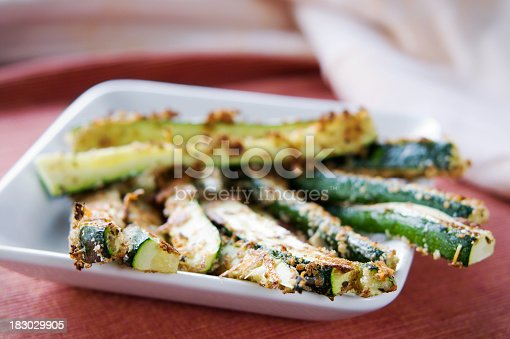 A plate full of baked zucchini fries.