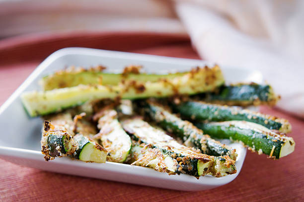 close-up of baked zucchini fries on white plate - courgette stockfoto's en -beelden
