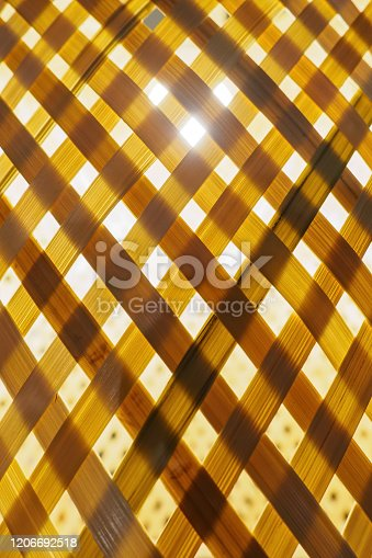 Close-up of bamboo woven stripes in the background of backlight, vertical view