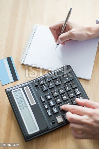 645670208istockphoto Closeup of Banker Using Calculator and Writing 891872472