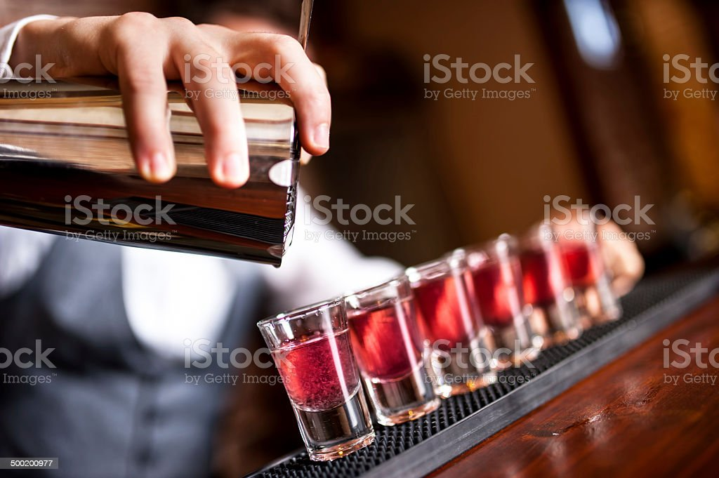 close-up of barman hand pouring alcohol into shot glasses stock photo