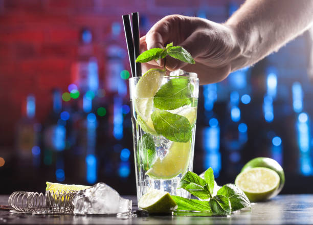 Closeup of barman making mojito cocktail on a bar lights background. Ingredients and utensils. stock photo