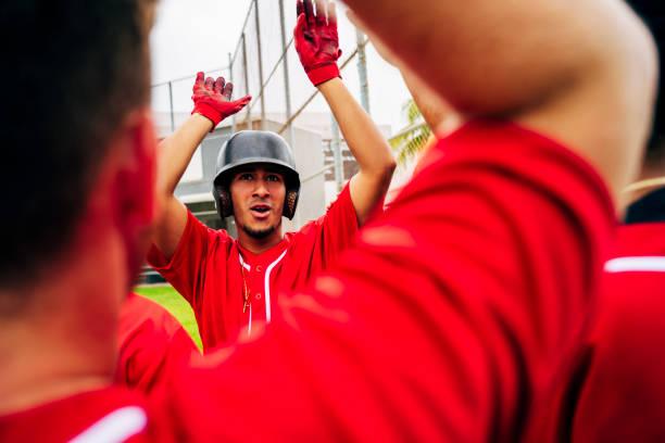 Close-up of baseball teammates congratulating scoring player stock photo