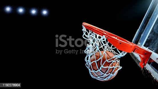 Close-up of basketball in hoop against black background.