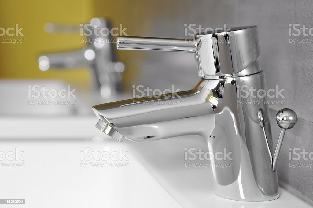 Close-up of bathroom water taps and sinks.
