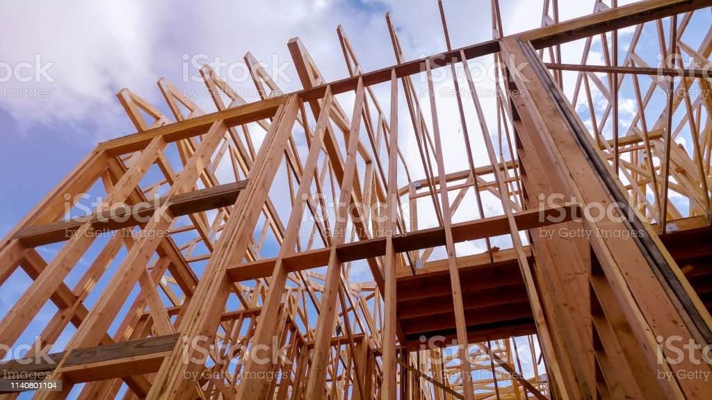 Closeup Of Beam Built Home Under Construction And Blue Sky