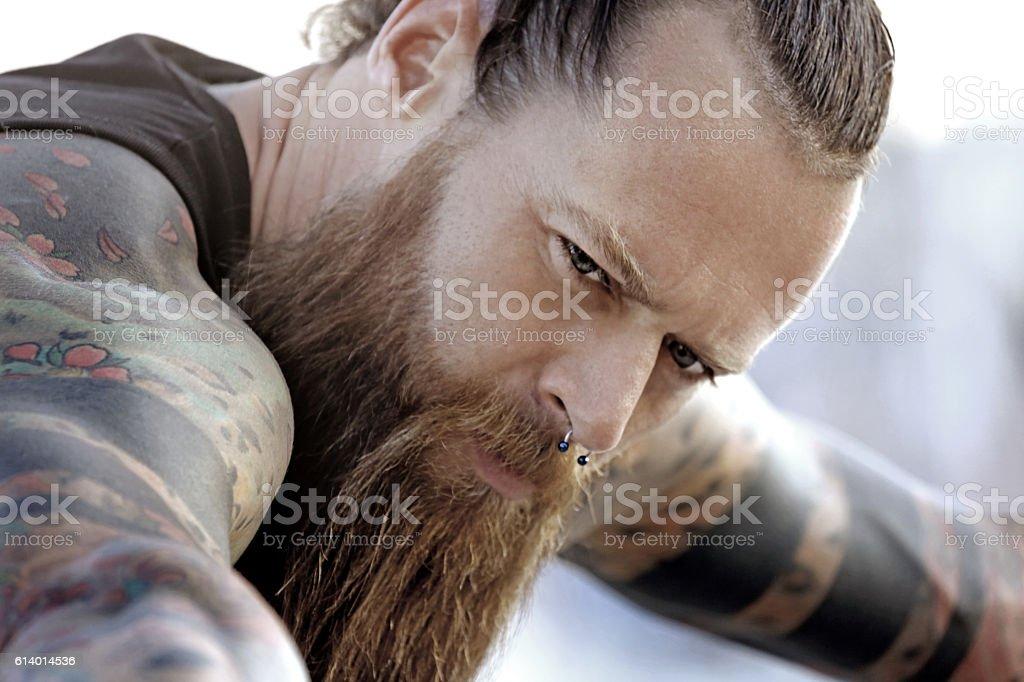 Close-up of bearded tattooed blue eyed handsome man stock photo