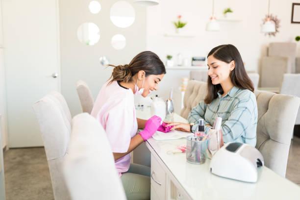 close up do beautician que aplica o prego no salão de beleza - manicure - fotografias e filmes do acervo