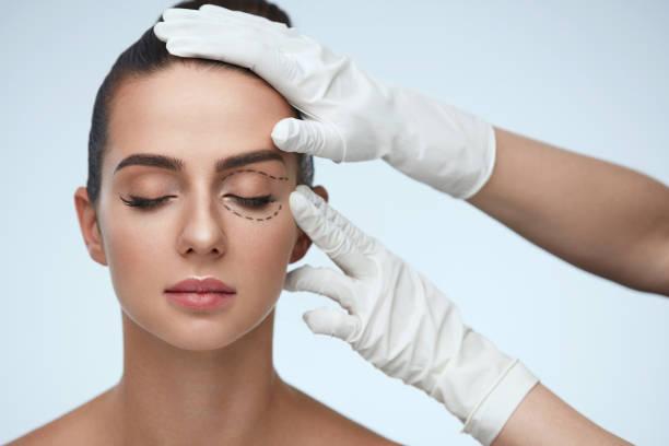 美容手觸摸年輕女性病人臉特寫 - 手術 個照片及圖片檔