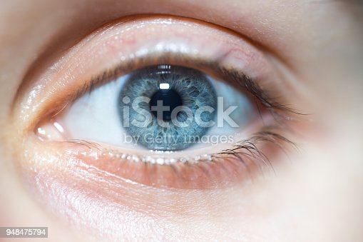A close-up shot of a beautiful blue woman eye looking at the camera.
