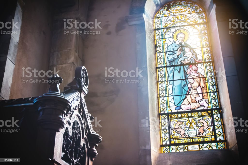 Close-up of beautiful christian stained glass transparent window from french church of Trevoux town indoor with sunlight stock photo