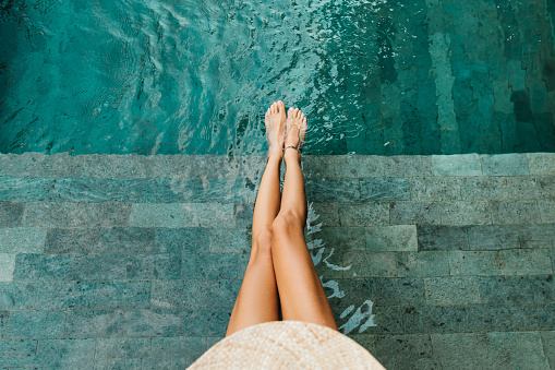Closeup of beautiful female legs in water of a pool summer concept