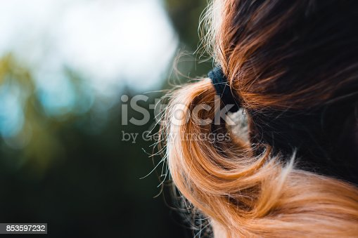 istock Close-Up Of Beautiful Girl With Orange Colored Hair Held In Ponytail Looking Away From The Camera 853597232