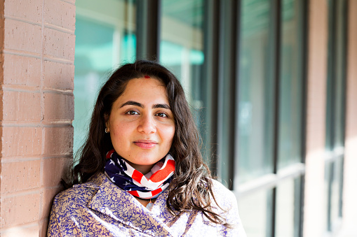 Proud and confident woman from Nepal dons her new country's flag colors around her neck during the Coronavirus pandemic.