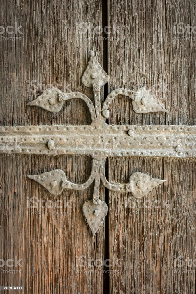 Close-up of beautiful old ancient metal ornament decoration on weathered brown wooden door. royalty-free stock photo