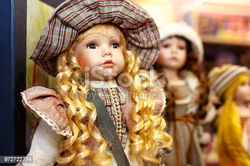 Close-up of beautiful porcelain doll with blond hair and blue eyes, sky blue vintage dress. Little princess games.