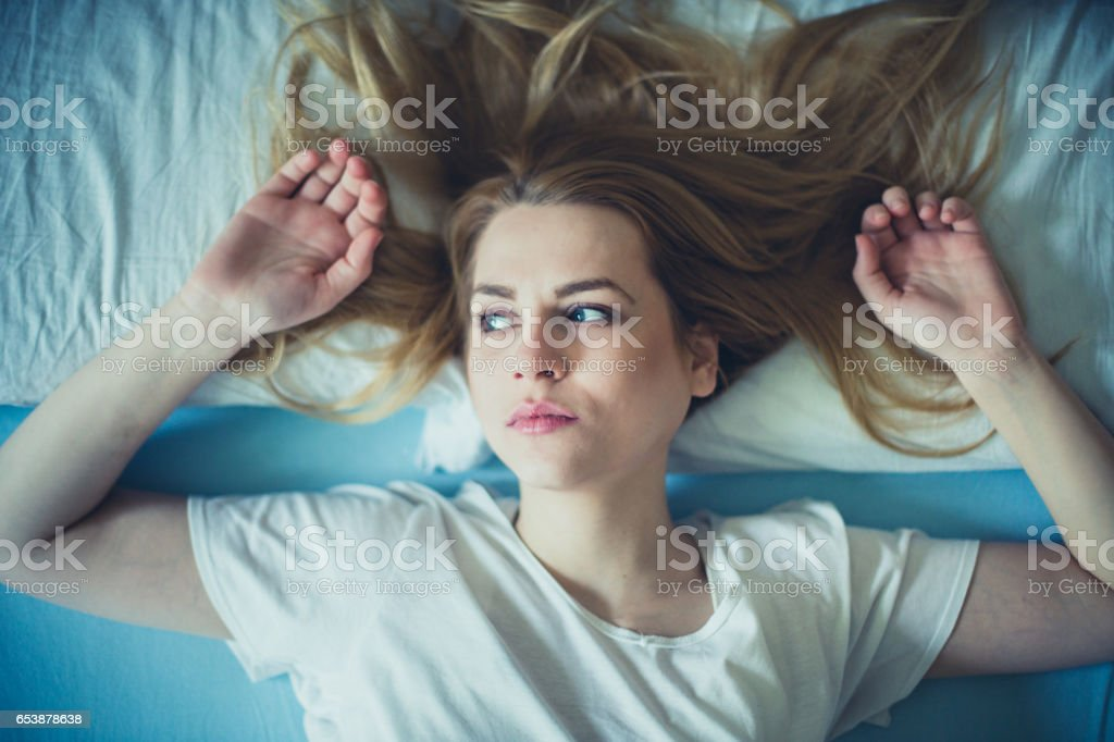 Close-up of beautiful sad woman in the bad stock photo