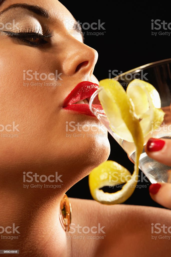 Close-up of beautiful woman drinking an alcoholic beverage royalty-free stock photo