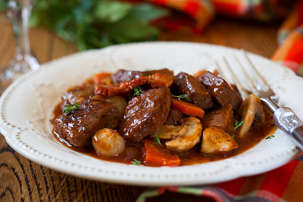 close-up of beef bourguignon served on white plate - braised stock pictures, royalty-free photos & images