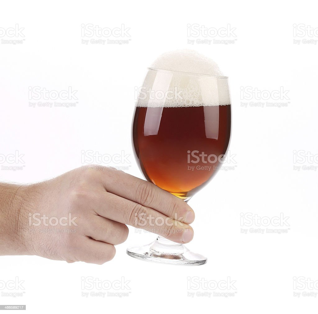 Closeup of beer glass in hand. stock photo