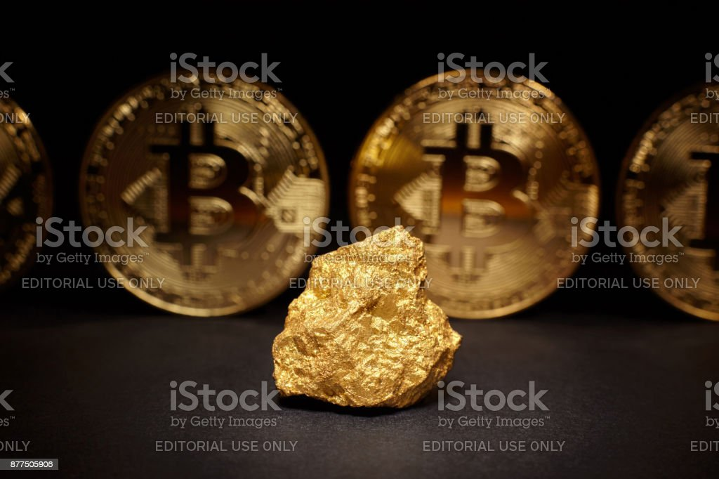 Closeup of big gold nugget and Gold Bitcoins Coins on black background stock photo