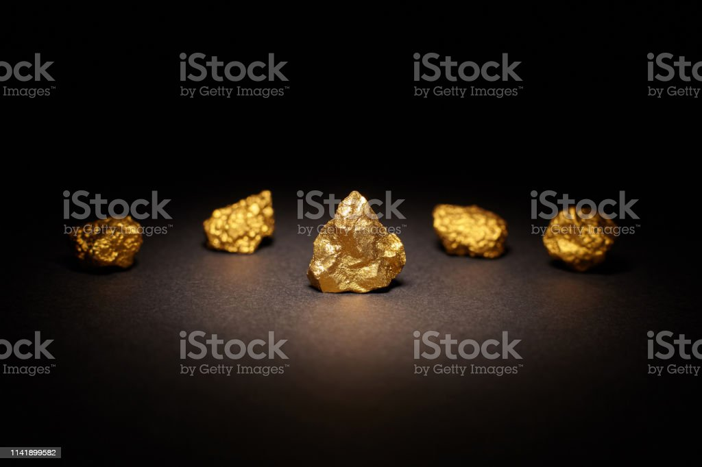 Closeup of big gold nugget on black background, finance concept